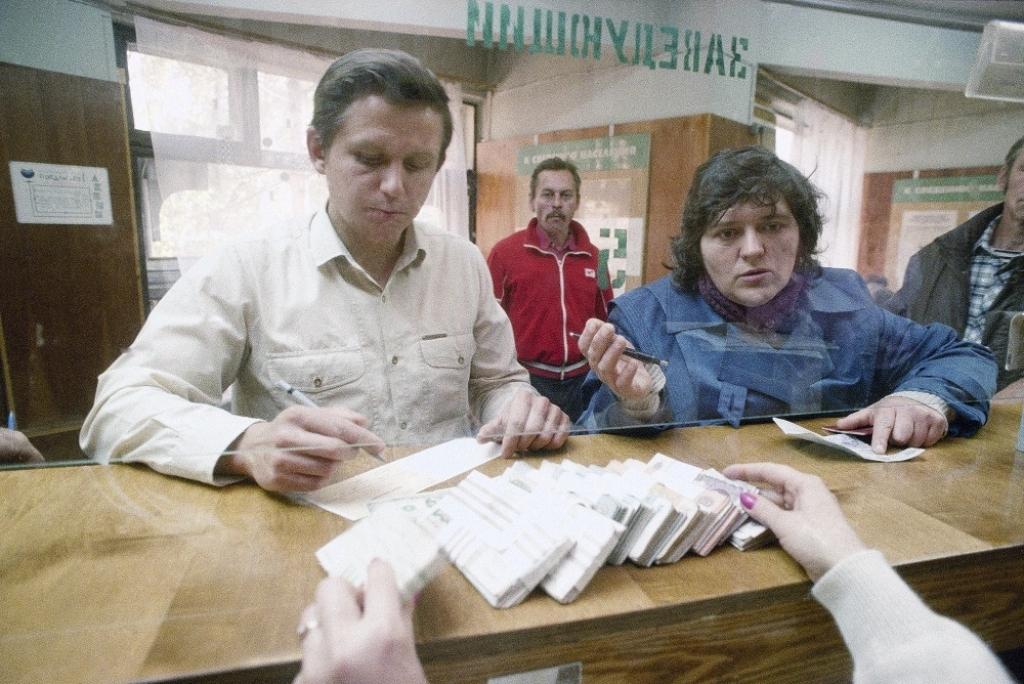 Москвичи меняют доллары на рубли в одном из местных банков в 'черны